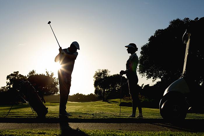 couple golfing at sunset